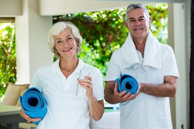 Счастливые старшие пары держа циновки тренировки Premium Фотографии