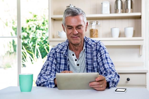 棚に対してデジタルタブレットを使用して年配の男性 Premium写真