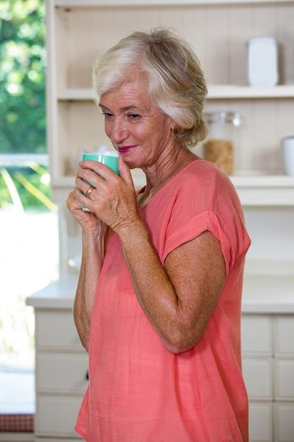 台所でコーヒーを飲んで思慮深い年配の女性 Premium写真