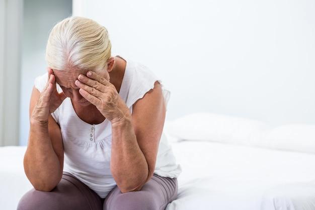 Старшая женщина с головой в руке сидит в спальне Premium Фотографии