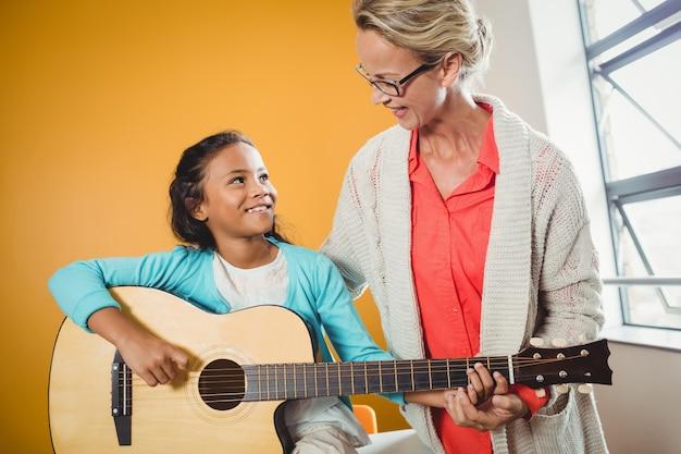 ギターの弾き方を学ぶ少女 Premium写真