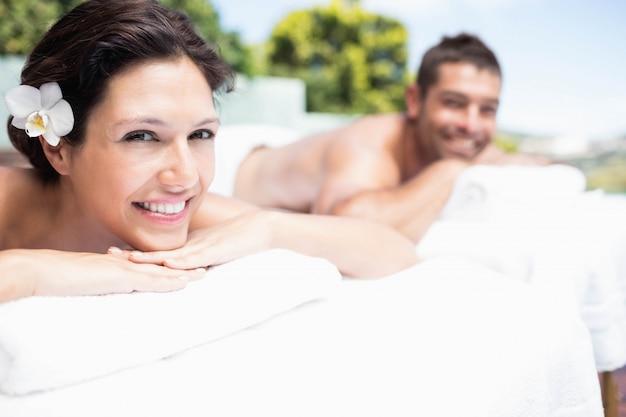 笑顔とスパのマッサージテーブルでリラックスした若いカップルの肖像画 Premium写真