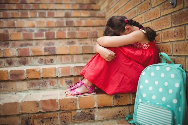 彼女の足に頭を持つ悲しい女子高生 Premium写真