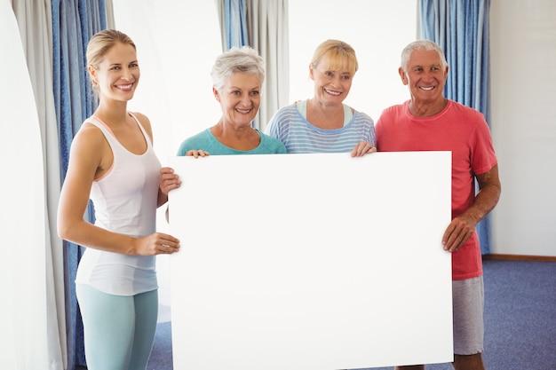 高齢者と白紙を保持しているフィットネスインストラクター Premium写真