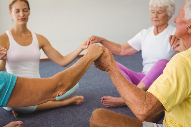 サークルで一緒に手を繋いでいる高齢者を集中 Premium写真