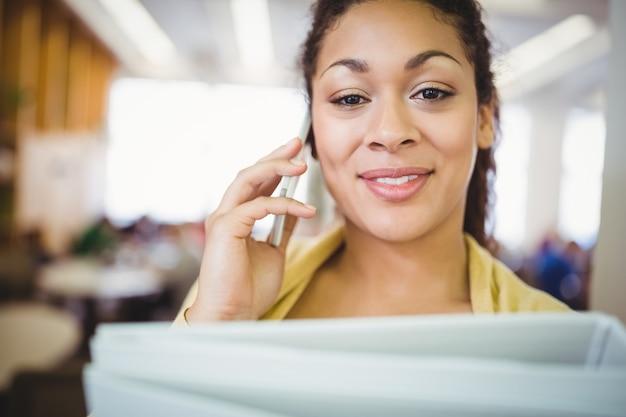 カフェテリアで携帯電話を使用しながらファイルを保持している実業家の肖像 Premium写真
