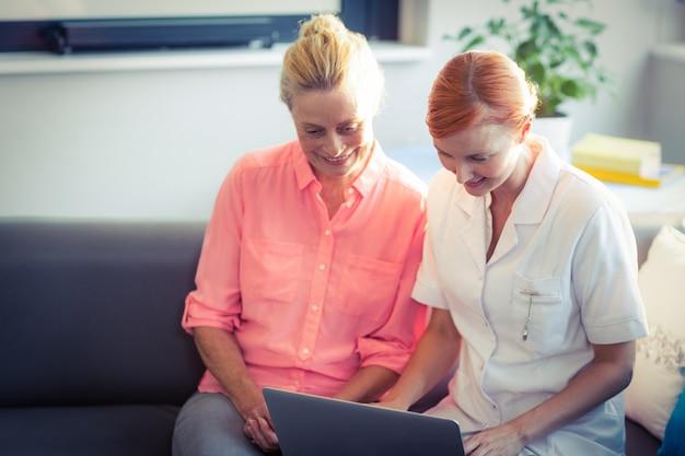 女性看護師とラップトップを使用して年配の女性 Premium写真