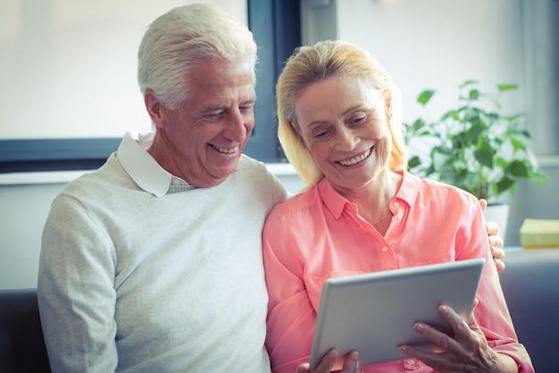 デジタルタブレットを使用しながら笑顔の年配のカップル Premium写真