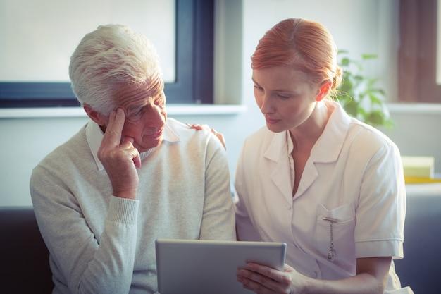 デジタルタブレットの年配の男性に医療レポートを示す女性看護師 Premium写真