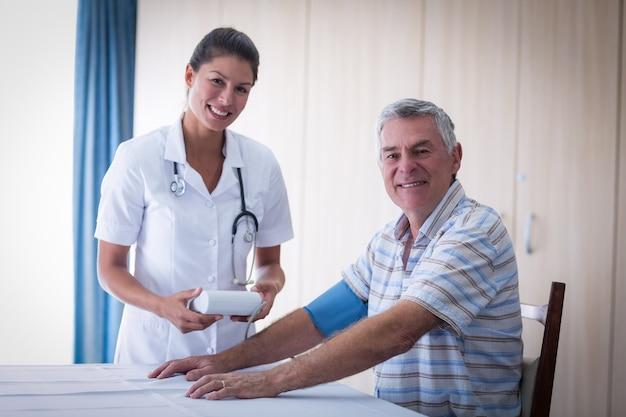 年配の男性の血圧をチェックする女性医師の肖像画 Premium写真