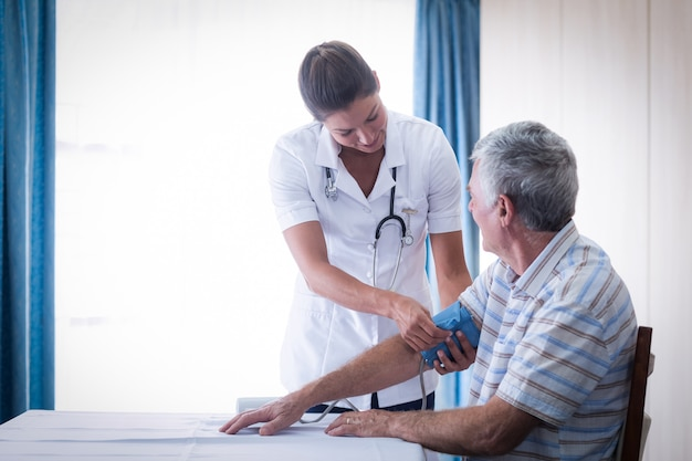 年配の男性の血圧をチェックする女医 Premium写真