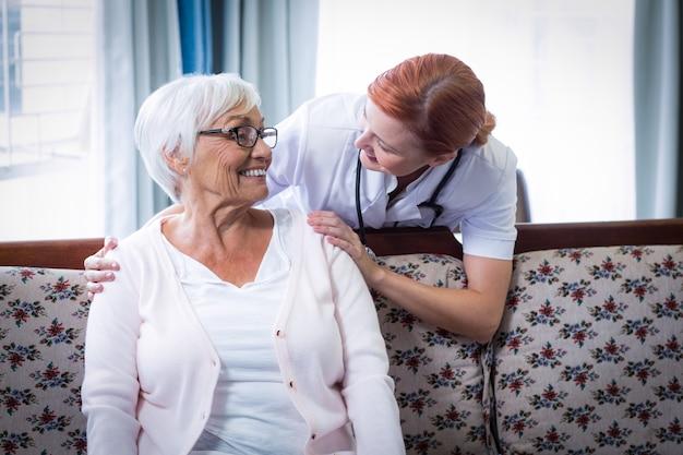Улыбающийся доктор разговаривает со счастливой старшей женщиной Premium Фотографии