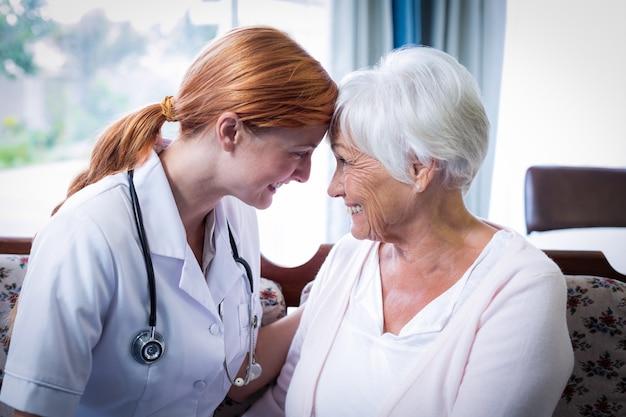 Улыбающийся доктор и пациент, глядя лицом к лицу Premium Фотографии