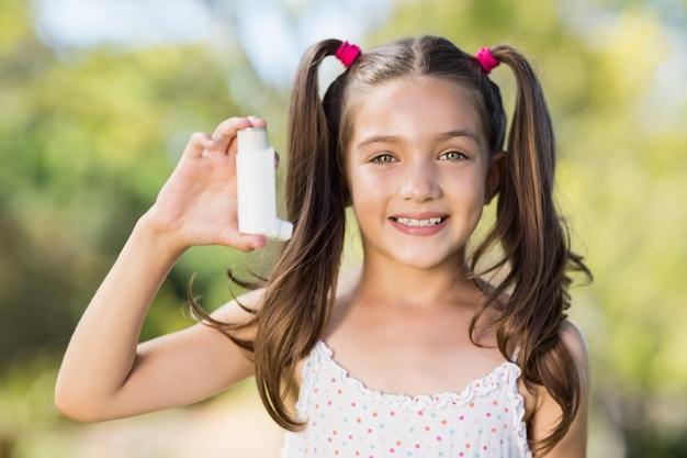 公園で喘息吸入器を保持している女の子 Premium写真