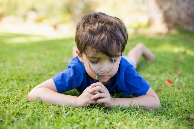 虫眼鏡で草を調べる少年 Premium写真