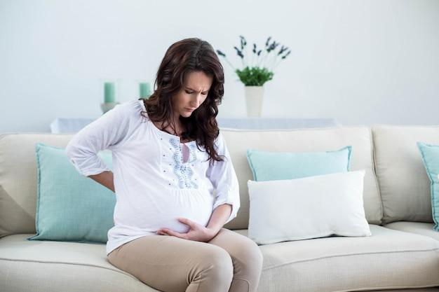 妊娠中の女性、リビングルームで背中の痛みを伴う Premium写真