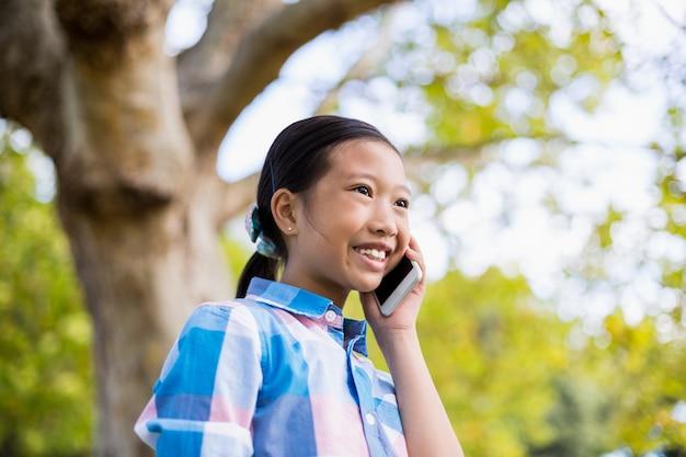 Улыбающаяся девушка разговаривает по мобильному телефону Premium Фотографии