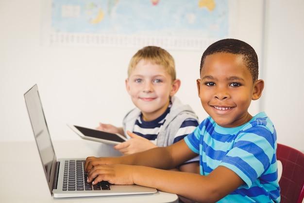 教室でノートパソコンとデジタルタブレットを使用して子供の肖像画 Premium写真