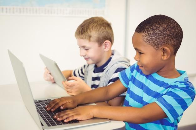 Школьники, используя ноутбук и цифровой планшет в классе Premium Фотографии