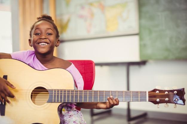 教室でギターを弾く笑顔の女子高生の肖像画 Premium写真