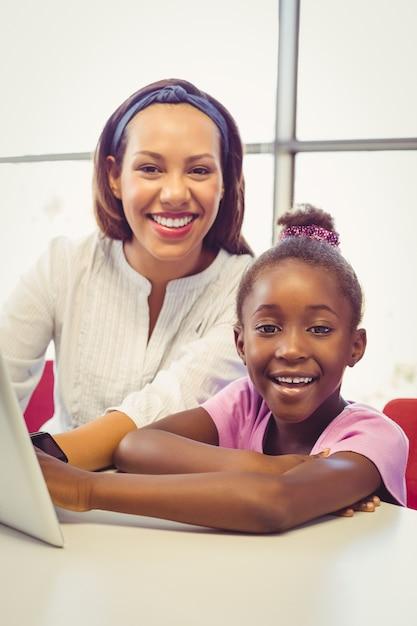 Учитель и школьница с помощью цифрового планшета в классе Premium Фотографии