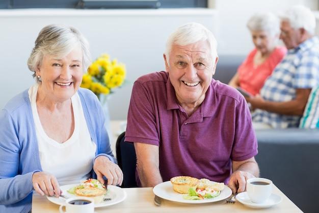 一緒に昼食を食べている年配のカップル Premium写真