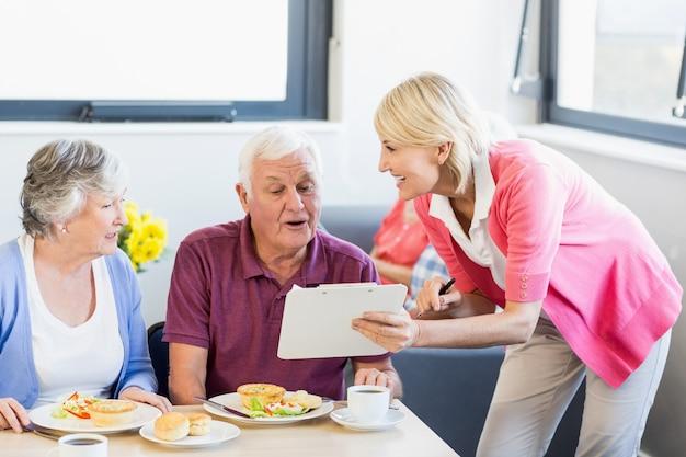 高齢者にクリップボードを示す看護師 Premium写真