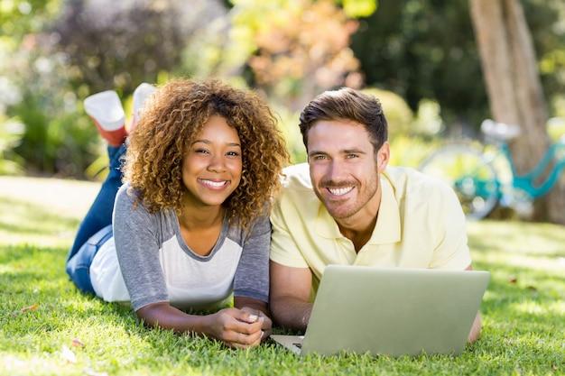 ラップトップを使用しながら笑顔のカップルの肖像画 Premium写真