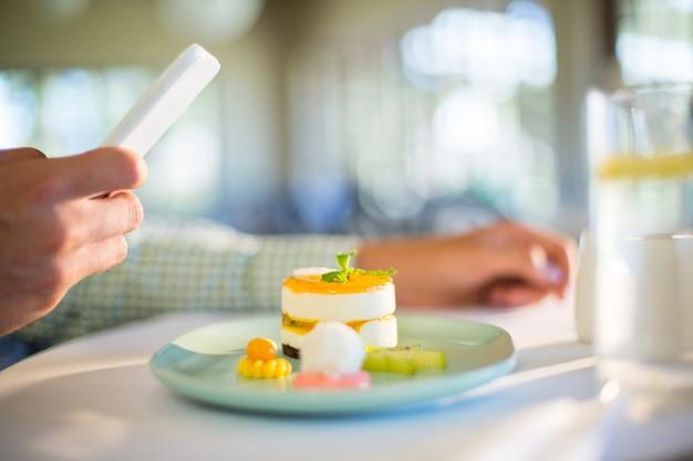 昼食をとりながら携帯電話を使用している人 Premium写真