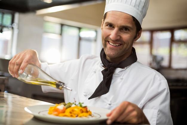 Портрет счастливого шеф-повара наливая оливковое масло на еду Premium Фотографии
