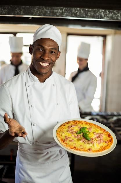 ピザを見せて笑顔のシェフの肖像画 Premium写真