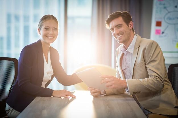 Бизнесмен и коммерсантка держа цифровую таблетку Premium Фотографии