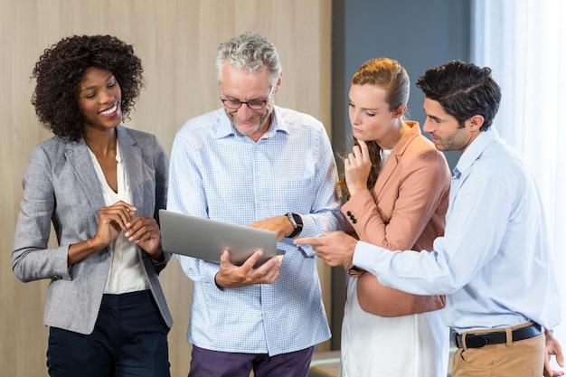 Улыбающиеся деловые люди обсуждают за ноутбуком Premium Фотографии