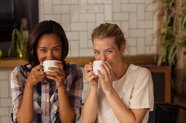 コーヒーを飲んでいる女性の友人の肖像画 Premium写真