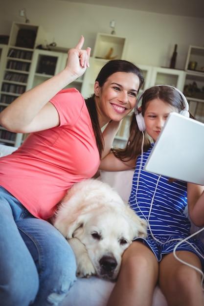 Счастливая мать и дочь, сидя с собакой и с помощью цифрового Premium Фотографии