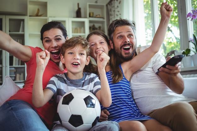 Возбужденная семья смотрит футбольный матч Premium Фотографии