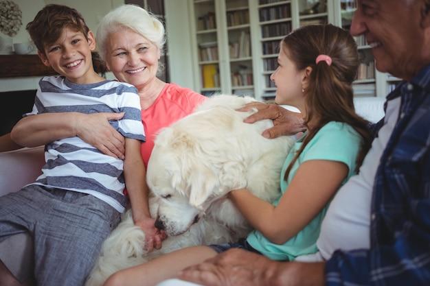 Бабушка и дедушка и внуки сидят на диване с собакой Premium Фотографии
