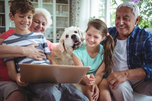 Бабушка и дедушка и внуки используют ноутбук в гостиной Premium Фотографии
