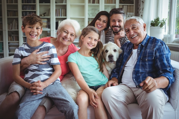 リビングルームのソファーに座っている幸せな家族の肖像画 Premium写真