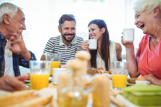 幸せなカップルと朝食をとりながら話している親 Premium写真