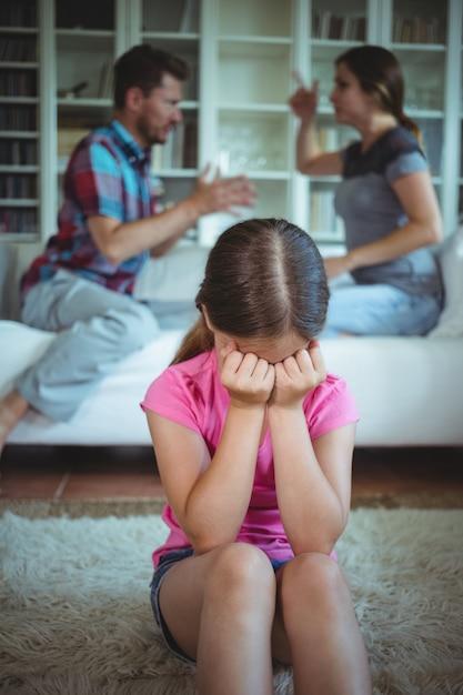 両親がリビングルームで主張しながら泣いている悲しい少女 Premium写真