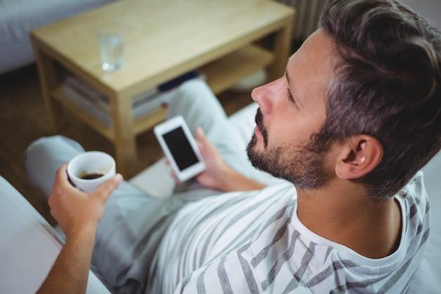 Отец, используя телефон, выпивая кофе в гостиной Premium Фотографии