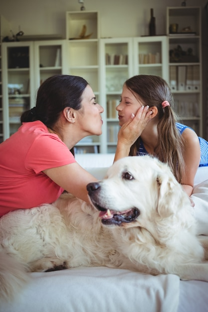 Мать и дочь сидят с собакой в гостиной Premium Фотографии