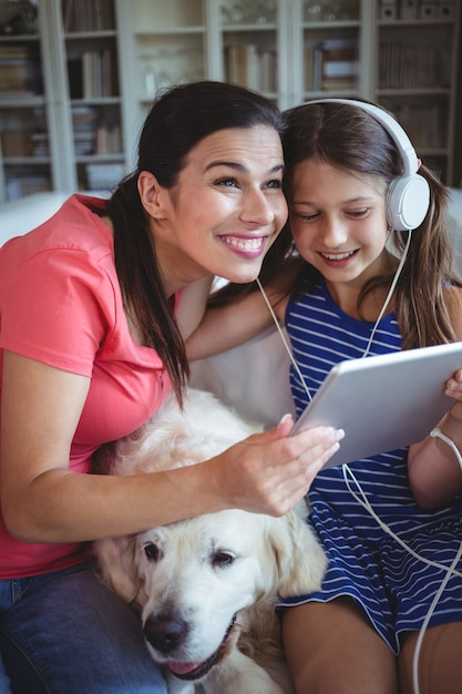 Счастливая мать и дочь, сидя с собакой и слушать музыку в наушниках Premium Фотографии