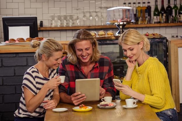 デジタルタブレットとスマートフォンを使用して友人 Premium写真
