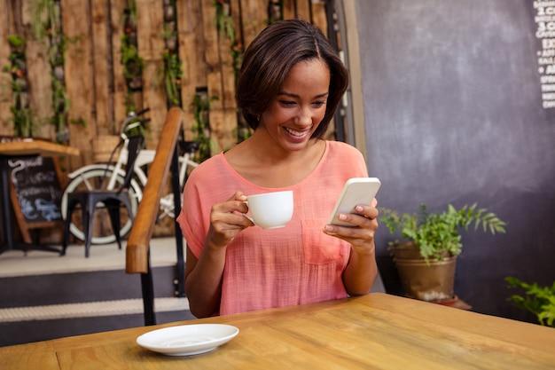 Женщина пьет кофе и с помощью смартфона Premium Фотографии