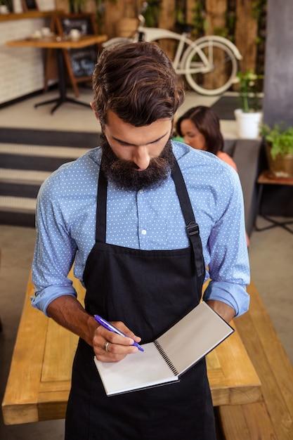 Официант принимает заказ в своей книге Premium Фотографии