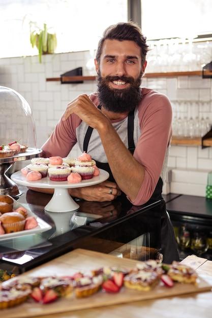 Мужчина позирует с пирожными Premium Фотографии