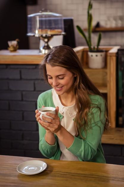 Улыбающиеся женщина, держащая чашку кофе Premium Фотографии