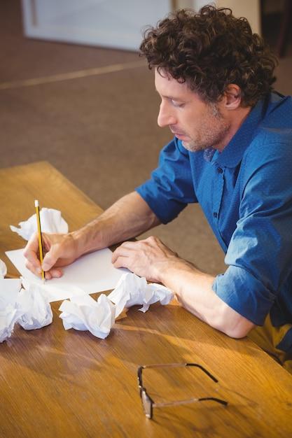 ビジネスマンは彼の論文に取り組んでいます Premium写真